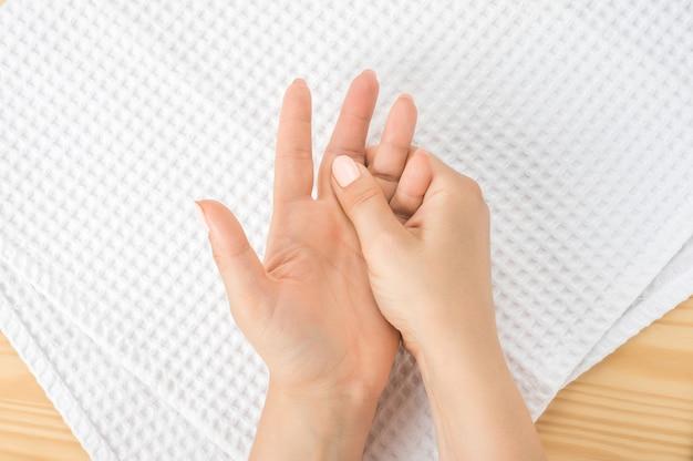 Femme caucasienne avec la main sur son doigt et sa paume malsains. automassage, syndrome de bureau et douleurs musculaires. une main féminine masse l'autre main allongée sur une serviette blanche avec la paume ouverte vers le haut