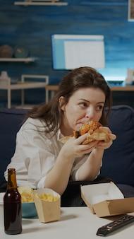 Femme caucasienne mangeant un hamburger dans un sac de livraison