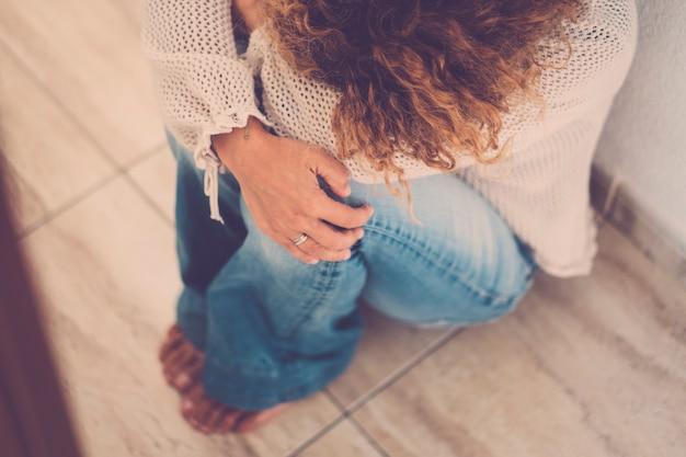 Femme caucasienne non reconnaissable assise seule et déprimée, portrait de jeune femme fatiguée. dépression à la maison s'asseoir par terre et se protéger en serrant son genou