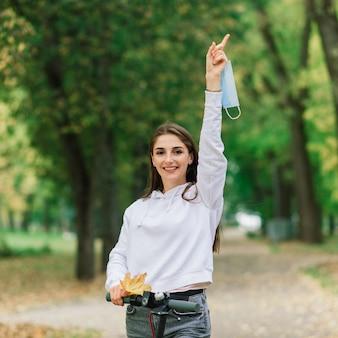 Femme caucasienne occasionnelle portant un masque protecteur équitation scooter électrique urbain dans le parc de la ville pendant la pandémie de covid. concept de mobilité urbaine.