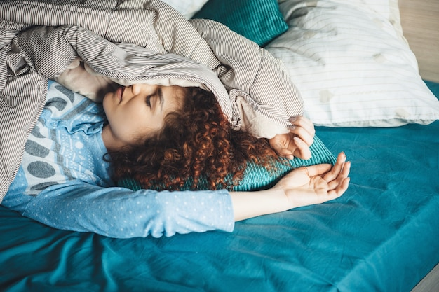 Femme caucasienne paresseuse aux cheveux bouclés et pyjama bleu dormir dans son lit recouvert d'une couette