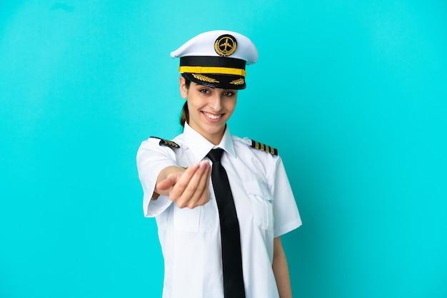 Femme caucasienne pilote d'avion isolée sur fond bleu invitant à venir avec la main. heureux que tu sois venu