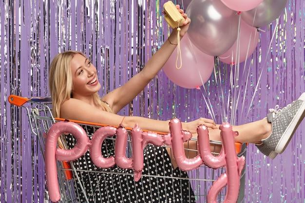 Femme caucasienne positive aux cheveux clairs, pose au chariot, fait selfie avec petit appareil photo, porte une robe à pois et des baskets, s'amuse à la fête