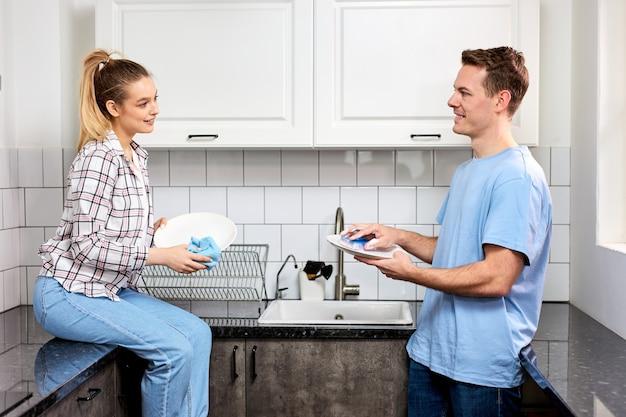 Femme caucasienne positive essuyant la vaisselle pendant que son mari se lave à la cuisine