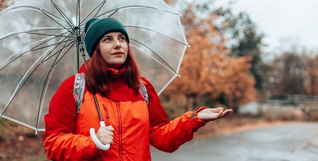 Une femme caucasienne positive avec un sac à dos et une veste rouge se promène dans les rues humides et pluvieuses sous un parapluie transparent. balade en forêt d'automne