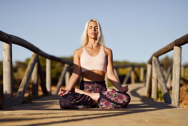 Femme caucasienne, pratiquer l'yoga sur un pont en bois.