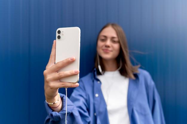 Femme caucasienne prenant un selfie avec son smartphone