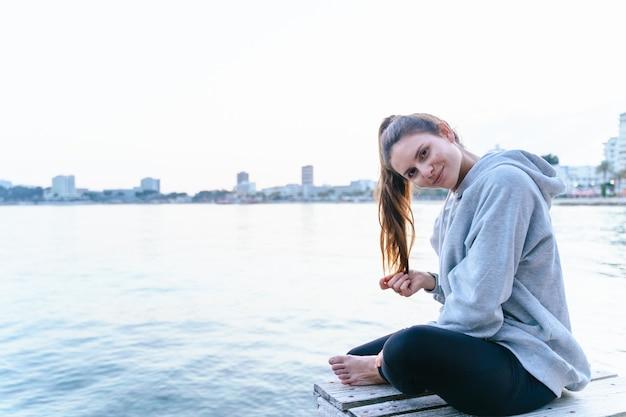 Femme caucasienne regardant droit devant elle tout en souriant et en se reposant sur un pont au-dessus de la mer