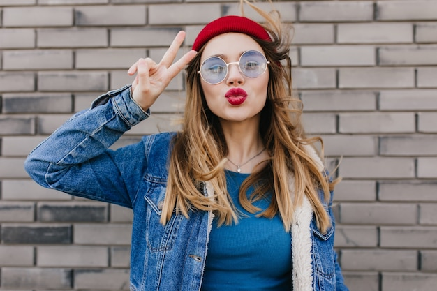 Femme caucasienne rêveuse dans des vêtements à la mode sur le mur de briques