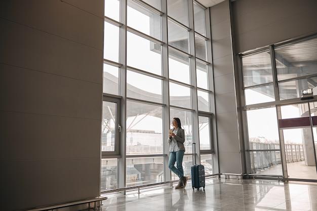 Une femme caucasienne se tient seule près des fenêtres panoramiques du terminal de l'aéroport avec des bagages