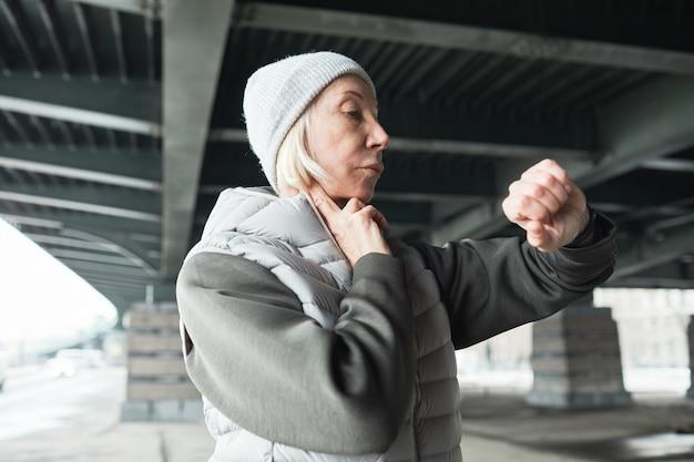 Femme caucasienne senior ciblée en chapeau gris et gilet touchant le cou tout en prenant le pouls à l'aide d'une montre-bracelet sous le pont à l'extérieur