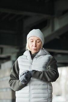 Femme caucasienne senior sérieuse en chapeau gris et gants debout sous le pont et vérifiant le pouls sur le tracker après avoir couru