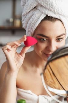 Femme caucasienne souriante enveloppée dans une serviette blanche appliquant du maquillage avec une éponge cosmétique dans l'appartement