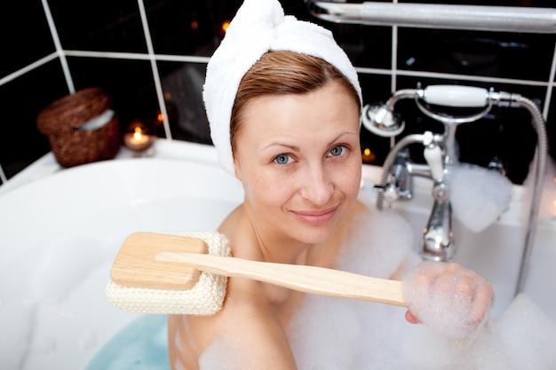 Femme caucasienne souriante prenant dans un bain moussant