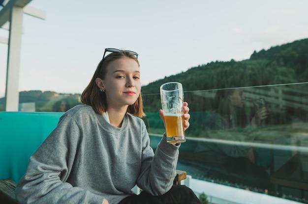 Femme caucasienne souriante tenant un verre de bière à une belle vue sur les bois