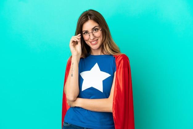 Femme caucasienne de super héros isolée sur fond bleu avec des lunettes et heureuse