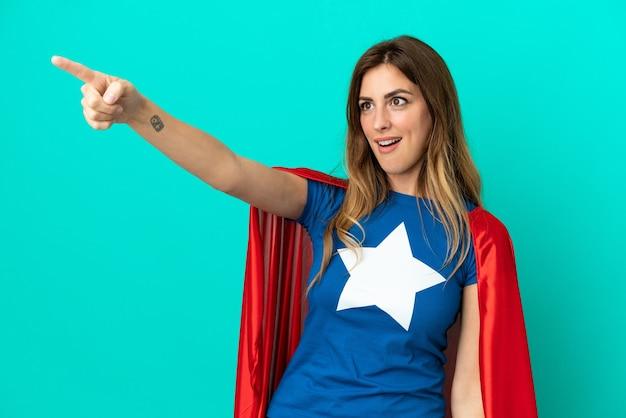 Femme caucasienne de super héros isolée sur fond bleu pointant vers l'extérieur