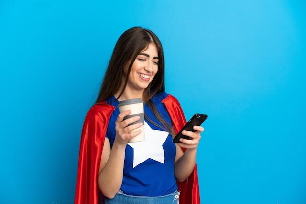 Femme caucasienne de super héros isolée sur fond bleu tenant du café à emporter et un mobile