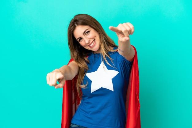 Une femme caucasienne de super héros isolée sur fond bleu vous montre du doigt tout en souriant