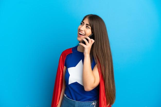 Femme caucasienne de super héros isolée sur le mur bleu gardant une conversation avec le téléphone portable