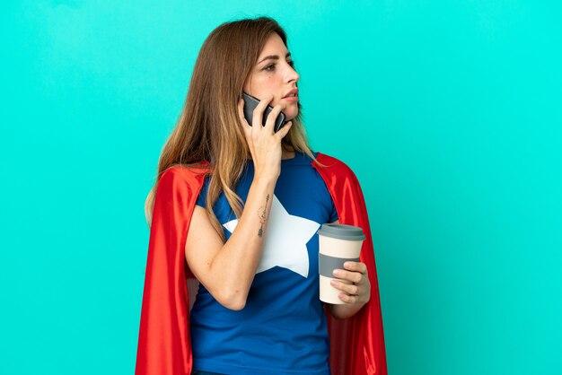 Femme caucasienne de super héros isolée sur un mur bleu tenant du café à emporter et un mobile