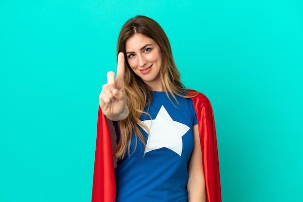 Femme caucasienne de super héros d'isolement sur le fond bleu montrant et soulevant un doigt