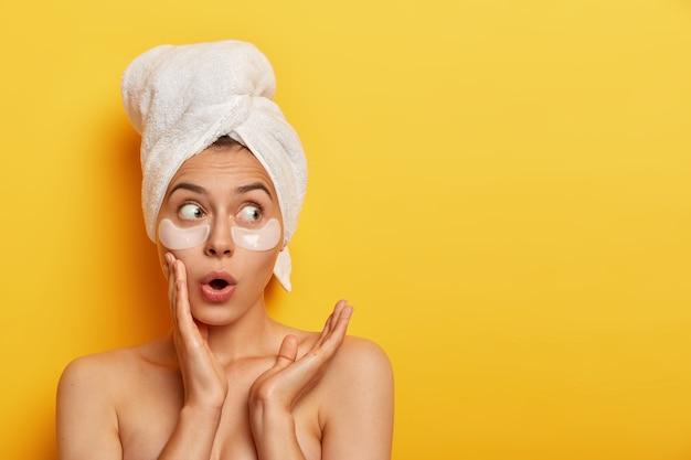 Une femme caucasienne surprise émotionnelle regarde avec une expression choquée de côté, se tient les épaules nues contre le mur jaune, a une peau douce impeccable, porte des taches sous les yeux, nettoie son teint