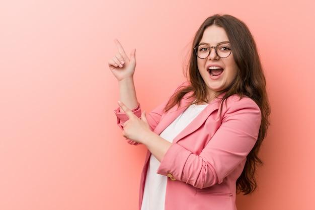 Femme caucasienne de taille plus jeune entreprise pointant avec les index
