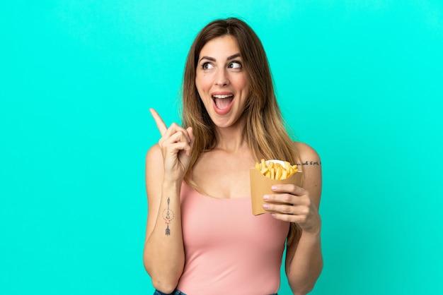 Femme caucasienne tenant des chips frites isolées sur fond bleu dans l'intention de réaliser la solution tout en levant un doigt vers le haut