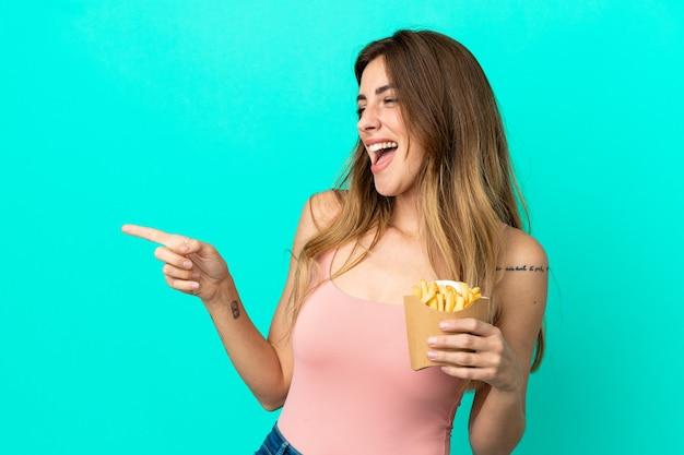 Femme caucasienne tenant des chips frites isolées sur fond bleu, pointant le doigt sur le côté et présentant un produit