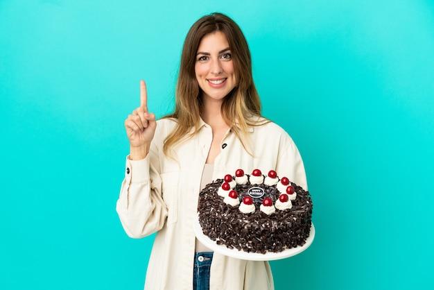 Femme caucasienne tenant un gâteau d'anniversaire isolé sur fond bleu montrant et levant un doigt en signe du meilleur