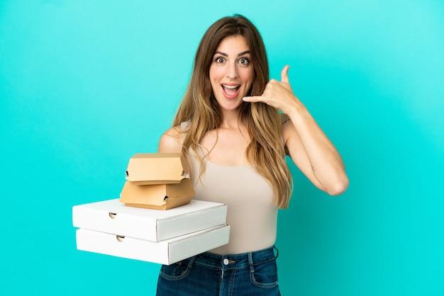 Femme caucasienne tenant des pizzas et un hamburger isolé sur fond bleu faisant un geste de téléphone. rappelle-moi signe
