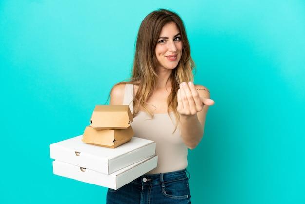 Femme caucasienne tenant des pizzas et un hamburger isolé sur fond bleu invitant à venir avec la main. heureux que tu sois venu