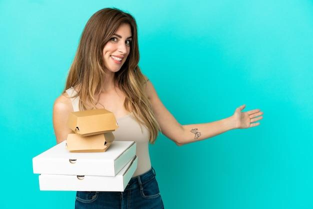 Femme caucasienne tenant des pizzas et un hamburger isolé sur fond bleu tendant les mains sur le côté pour inviter à venir
