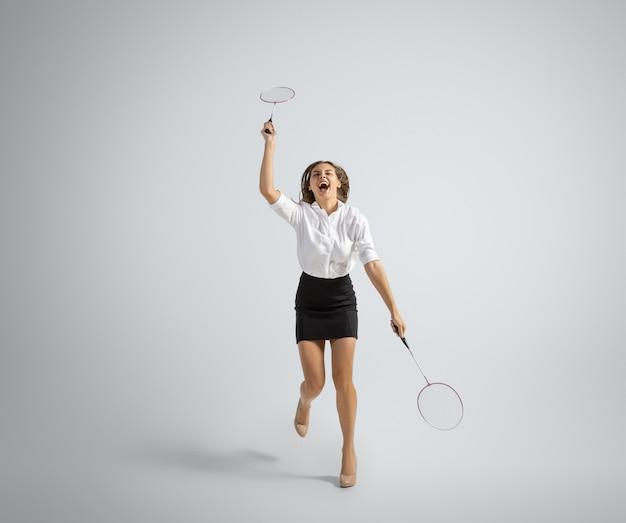 Une femme caucasienne en tenue de bureau joue au badminton sur fond gris