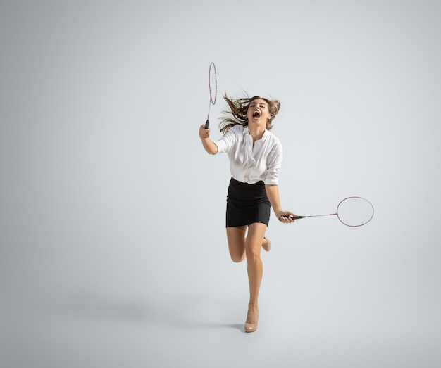 Une Femme Caucasienne En Tenue De Bureau Joue Au Badminton Isolé Sur Un Mur Gris Photo gratuit