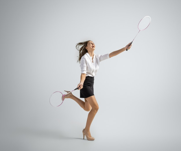 Une femme caucasienne en tenue de bureau joue au badminton isolé sur un mur gris