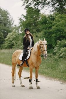 Femme de cavalier montant son cheval dans un ranch. la femme a les cheveux longs et des vêtements noirs. cavalière femelle sur son cheval brun.