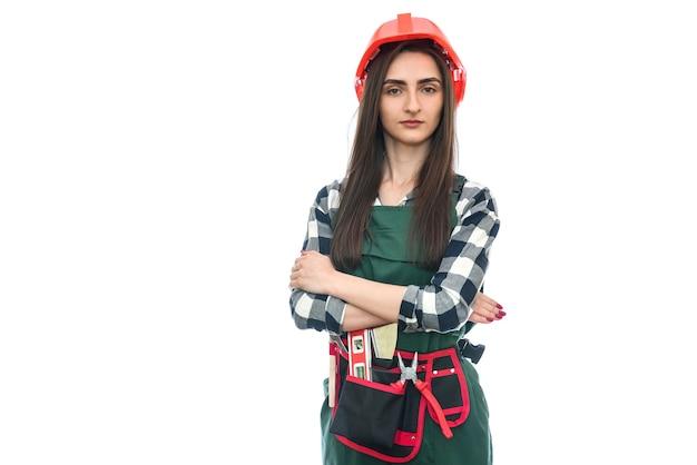 Femme en ceinture à outils et combinaison isolée sur mur blanc