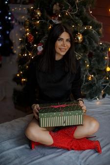 Femme célèbre le nouvel an devant l'arbre de noël et s'assoit avec le cadeau à portée de main