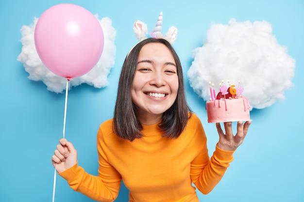 Une femme célèbre son 26 e anniversaire a une humeur festive tient un gâteau et un ballon gonflé sourit joyeusement vêtue d'un pull orange décontracté isolé sur bleu