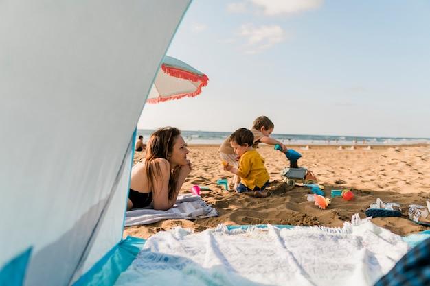 Femme célibataire du millénaire profitant d'un après-midi ensoleillé à la plage en été ou au printemps avec ses fils