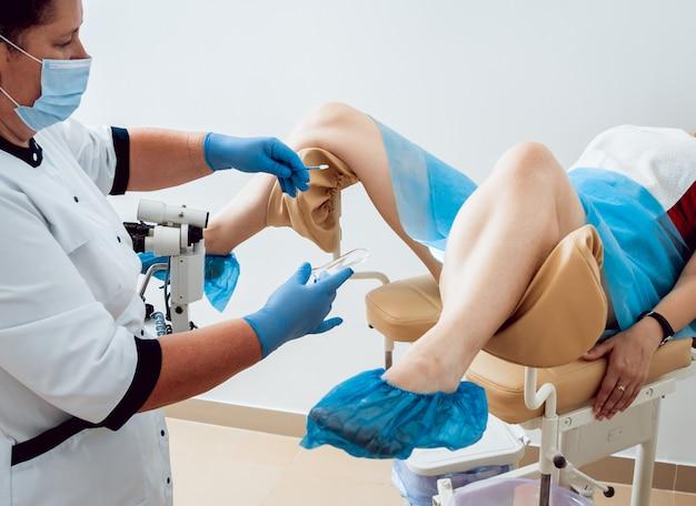 Femme en chaise gynécologique lors d'un contrôle gynécologique avec son médecin.
