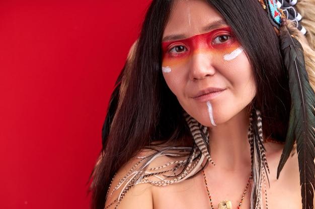 Femme chaman avec des plumes sur la tête souriant, ayant des peintures indiennes ethniques sur le visage. mur rouge isolé