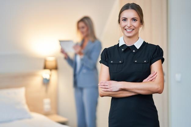 Femme de chambre adulte et directeur de l'hôtel nettoyant la chambre