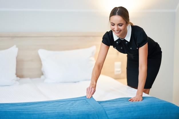 Femme de chambre faisant le lit dans une chambre d'hôtel