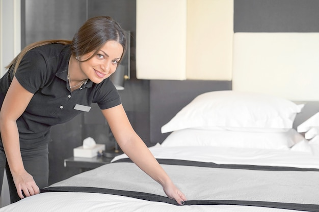 Femme de chambre faisant le lit