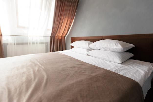 Femme de chambre avec des oreillers et des draps blancs propres dans la salle de beauté.
