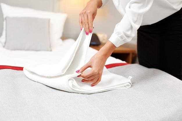Femme de chambre pliant des serviettes fraîches dans la chambre d'hôtel