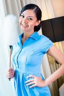 Femme de chambre saupoudrage dans chambre d'hôtel asiatique